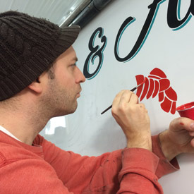 hand painting a boat stern